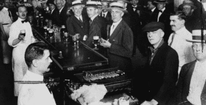 Black and white image of men in a speakeasy bar holding drinks. East Village Prohibition Pub Crawl